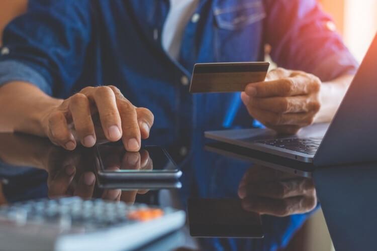 Homem fazendo compra com cartão de crédito pelo celular.