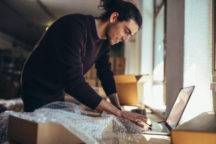 Homem mexendo em computador com caixas de papelão ao redor.