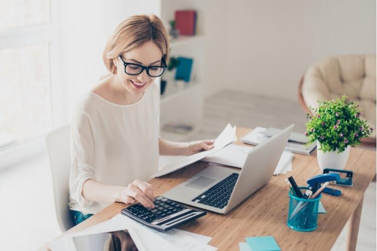 Mulher fazendo contas em calculadora, com notebook e papéis ao redor.