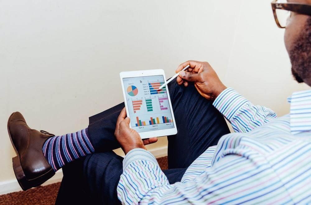 Homem analisando gráficos em um tablet.