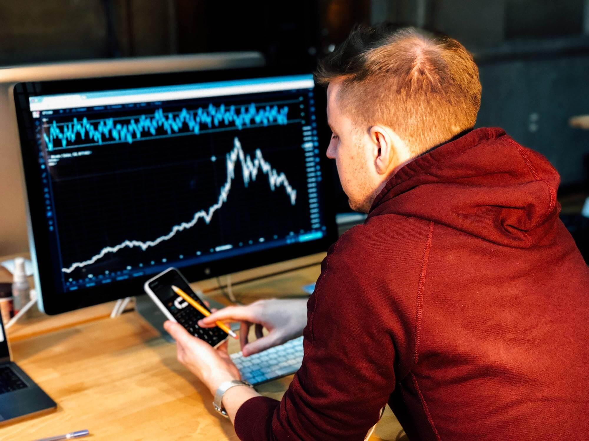 Homem analisando dados do e-commerce e fazendo contas.