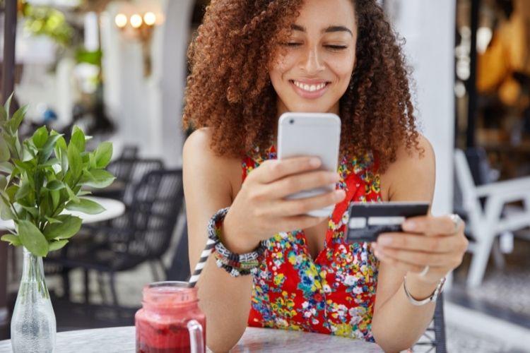 Mulher com cartão de crédito em uma mão e, na outra, um celular.