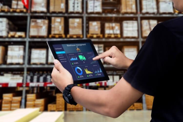 Homem analisando gráficos sobre o estoque para a Black Friday em tablet.