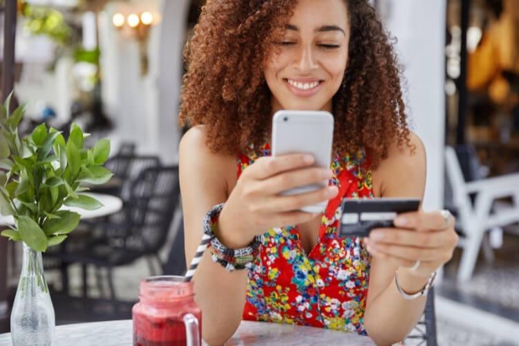 Mulher realizando compra com cartão de crédito pelo celular.