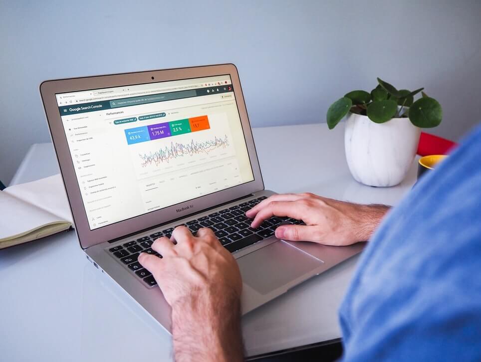 Homem navegando no Google Search Console, olhando resultados de SEO da Black Friday.