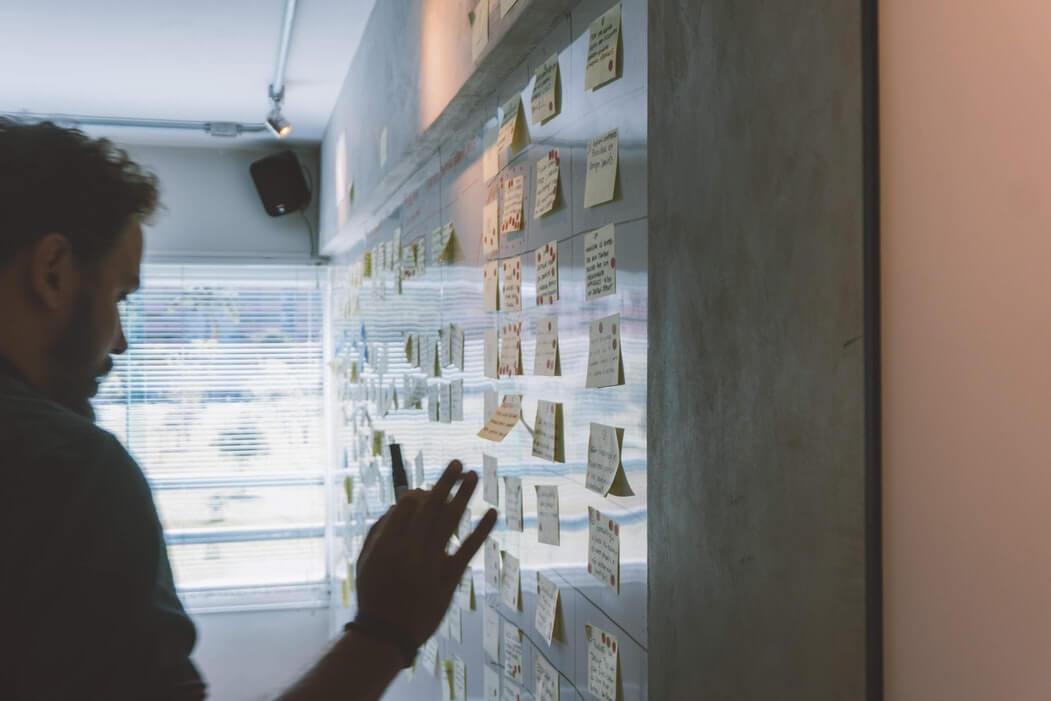 Homem colando post its na parede enquanto planeja a Black Friday no e-commerce.