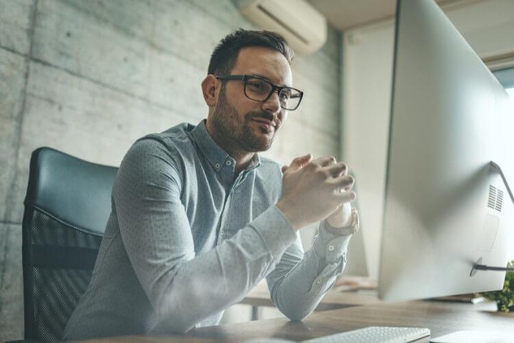 Homem de camisa social com as mãos cruzadas olhando para computador.