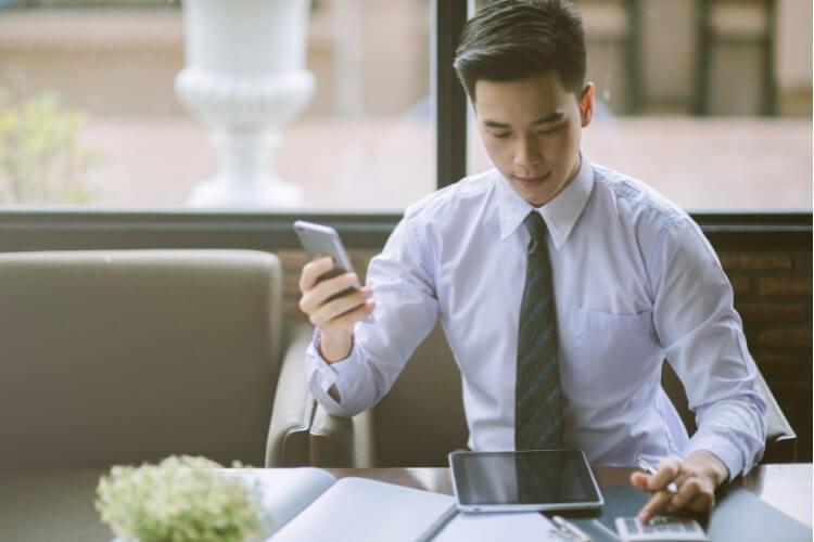 Homem de camisa e gravata realizando contas em calculadora.