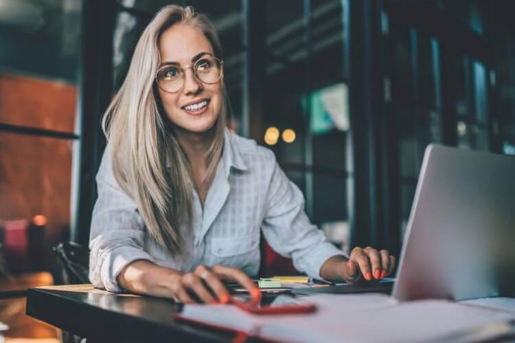 Mulher sorrindo enquanto atende cliente.