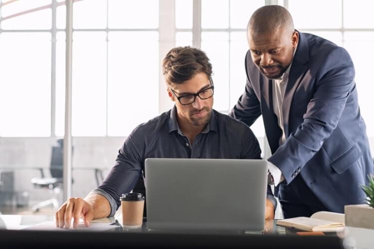 Homens de negócios analisando dados em um notebook.