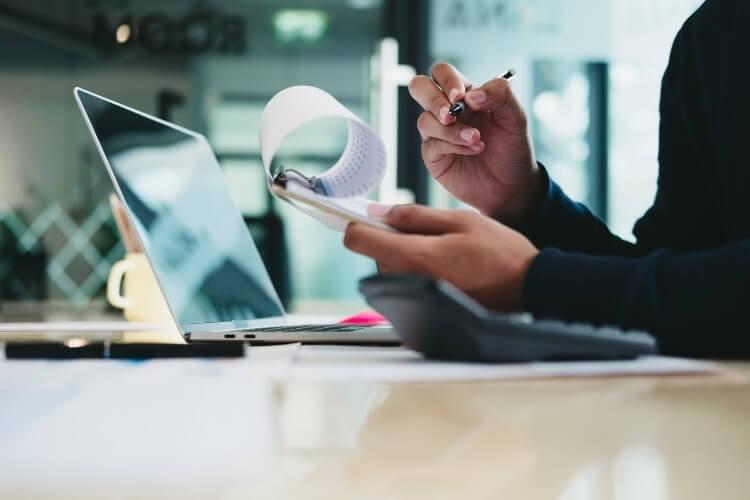 Homem com bloco de notas e caneta nas mãos, em um escritório.