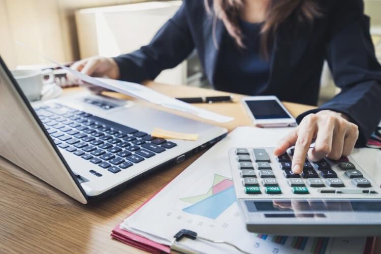 Mulher fazendo contas com calculadora e notebook.