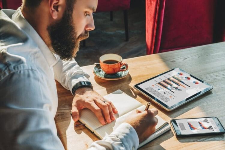 Homem bebendo café e realizando anotações em um caderno.