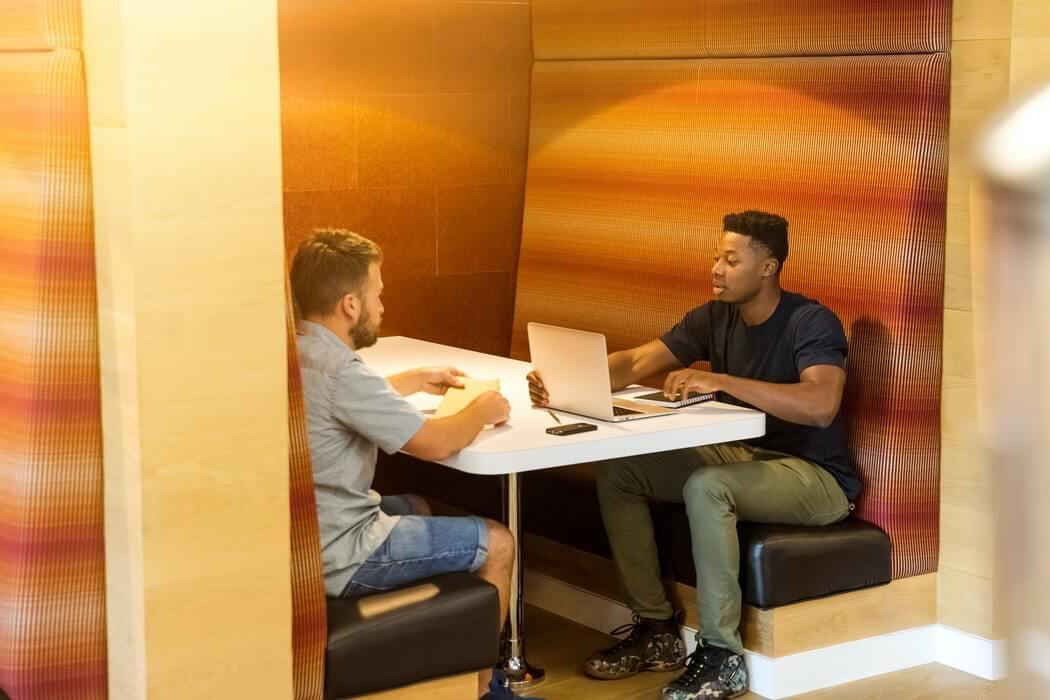 Homens trabalhando e conversando em posto de trabalho.