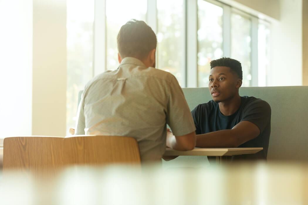 Homens conversando em mesa de trabalho.