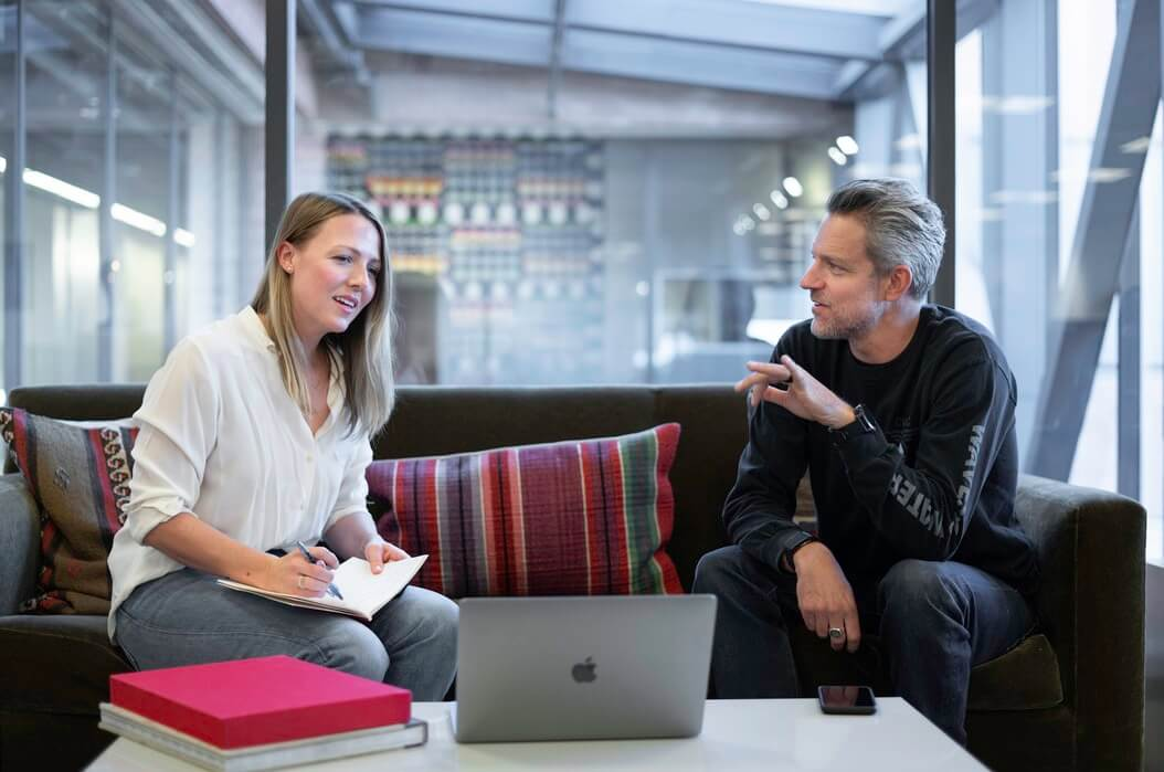 Homem e mulher conversando em reunião de empresa.