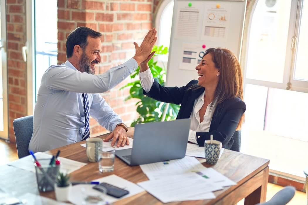 Homem e mulher de roupa social batendo as mãos em comemoração.